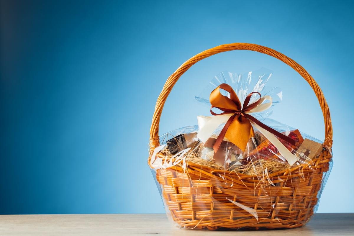 Photo of large brown gift basket wrapped in plastic and tied with a brown bow.