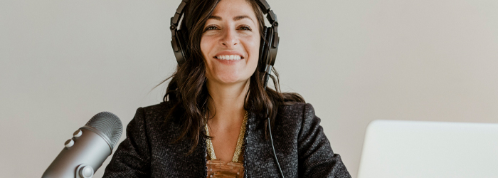 Woman with headset and microphone recording a podcast