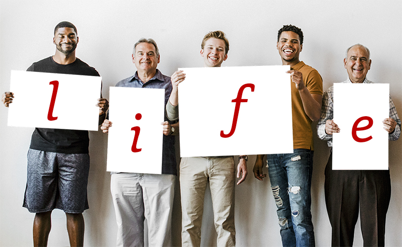 Four diverse men holding white signs with the letters L I F E